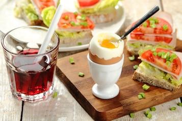 Jajko na miękko, kanapka z szynką z indyka, pomidor ze szczypiorkiem, sok z czarnej porzeczki