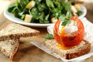 Jajko zapiekane w pomidorze, sałatka ze szpinaku i gruszki, chleb słonecznikowy