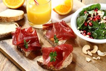 Kanapka z pastrami wołowymi, sałatka ze szpinaku z ziarnem granatu i orzechami, sok pomarańczowy